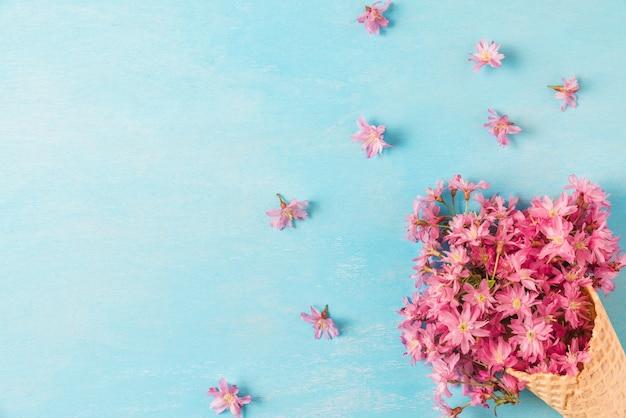 Blühende blumen der frühlingsrosa-kirsche im waffelkegel. flach liegen. draufsicht mit kopierraum