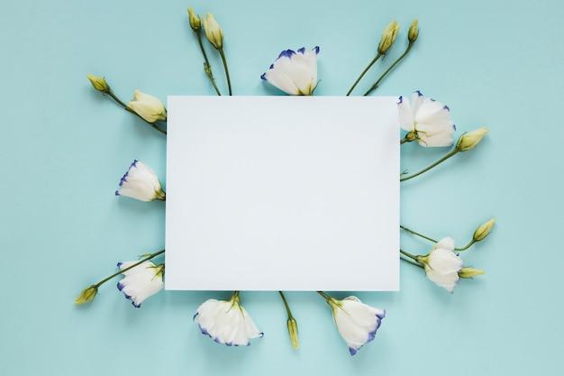 Blühende frühlingsblumen, die ein leeres blatt papier umgeben