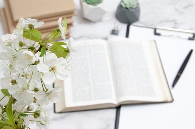 Blühende kirsche auf dem hintergrund einer offenen bibel auf dem desktop