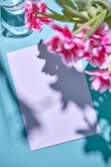 Blühende komposition mit rosa tulpen in einer glasvase