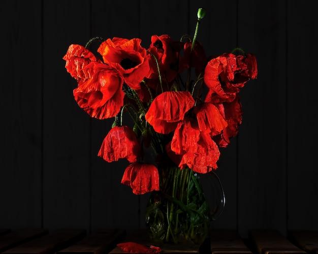 Blühende mohnblumen in einer glasvase im dunkeln