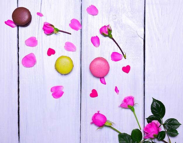 Blühende rosa rosen und drei makronen