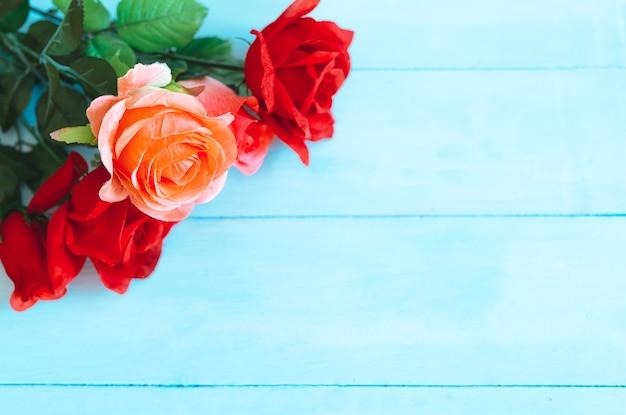 Blühende rosen auf blauem grund. platz für text