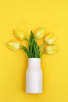 Blühende tulpenblüten in kleiner weißer vase auf gelb
