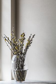 Blühende weidenblumen in einem blumenstrauß in einer vase auf dem tisch. frühlingshintergrund