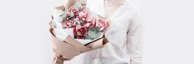 Blühende zarte blumen der rosa orchidee in den händen der frau auf hellem hintergrund mit kopienraum. moderner blumenstrauß zum verschenken für ihre mutter oder freund.