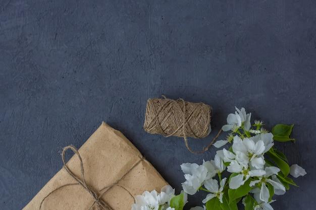 Blühende zweige der kirsche, apfelbaum auf einem grauen hintergrund. blumenkomposition. hübsche geschenkbox mit braunem bastelpapier umwickelt und mit jute verziert, draufsicht