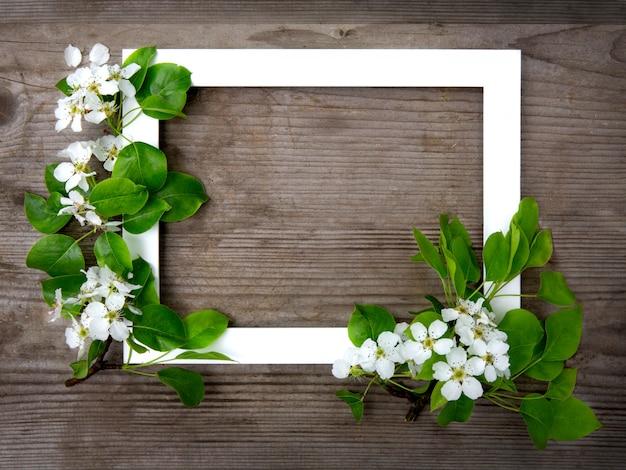 Blühender apfelbaumzweig neben einem weißen rahmen auf einem hölzernen hintergrund. frühlingsstimmung. osterkarte oder rahmen. layout, flach liegen.