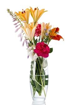 Blühender blumenstrauß in einer transparenten vase mit wasser. isoliert auf weißem hintergrund.