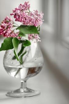 Blühender fliederbündel im unscharfen weinglas auf weißem hintergrund