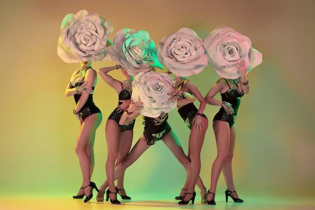 Blühender garten. junge tänzerinnen mit riesigen blumenhüten im neonlicht an der farbverlaufswand.