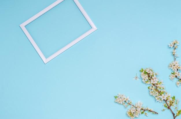 Blühender kirschzweig mit weißen blumen und einem rahmen mit platz für text auf blauem hintergrund. saisonalitätskonzept, frühling. flache lage, kopierraum. sicht von oben.
