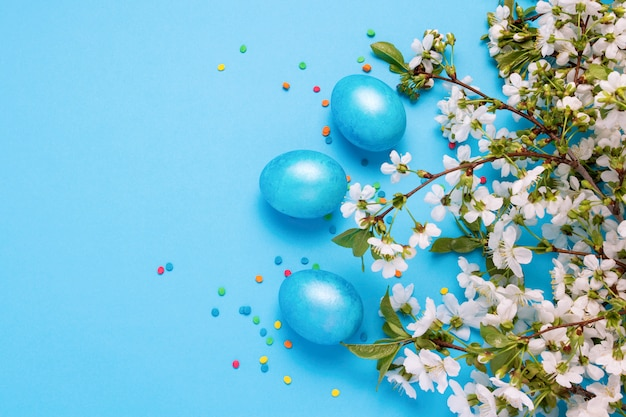 Blühender kirschzweig, ostblaue eier und mehrfarbiges pulver auf dem blauen hintergrund