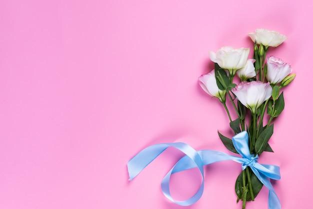 Blühender rosa eustoma des blumenstraußes auf rosa hintergrund, ebenenlage. valentinstag, geburtstag, mutter oder hochzeit grußkarte