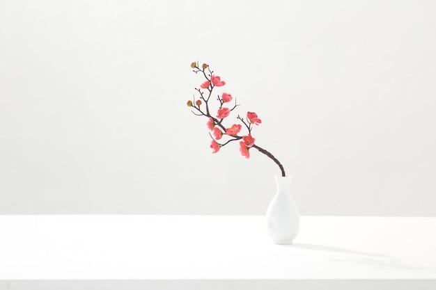 Blühender rosa kirschzweig in der weißen vase auf weißem hintergrund