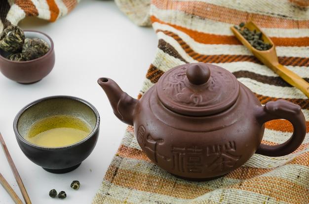 Blühender tee mit blumenball und oolong teestaubtee gegen weißen hintergrund