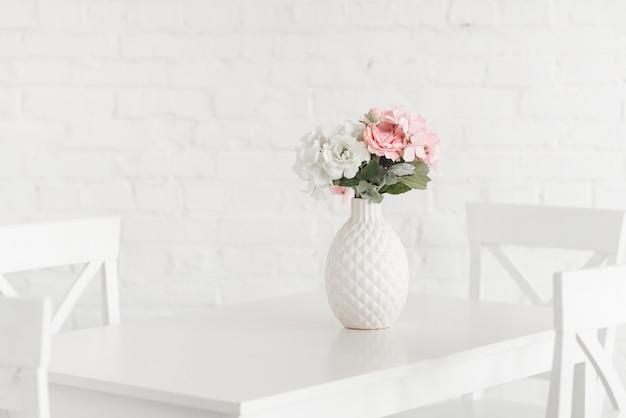 Blühender weißer vase auf tabelle gegen backsteinmauer