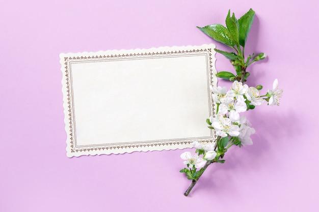 Blühender zweig eines apfelbaums neben einer postkarte auf einem rosa hintergrund. frühlingsstimmung. flaches layout. osterkarte oder rahmen.