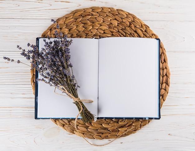 Blüht blumenstrauß auf leerem notizbuch auf tabelle