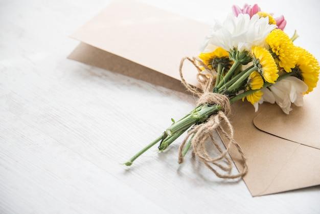 Blüht blumenstrauß mit kartenanmerkung und umschlag auf einem weißen hölzernen rustikalen hintergrund