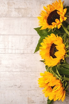 Blüht zusammensetzung von gelben sonnenblumen auf einem weißen holz