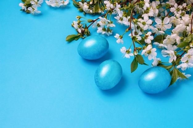 Blüte kirsche und ostern blaue eier auf dem blauen hintergrund.