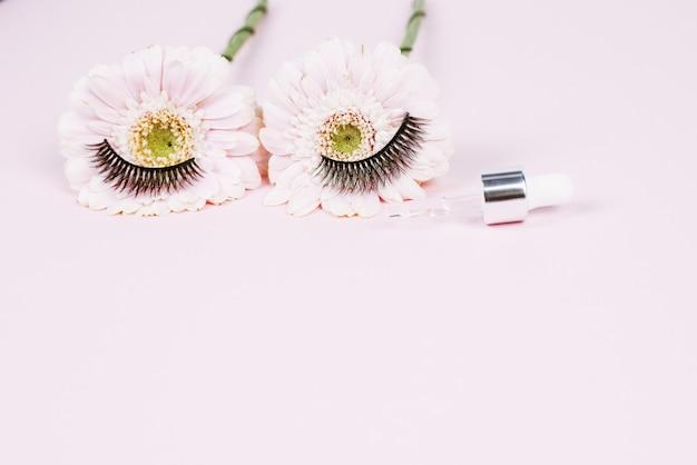 Blüten in form von menschlichen augen mit wimpern neben einer pipette mit feuchtigkeitsspendendem serum für die haut um die augen. medizinische geräte und augentropfen