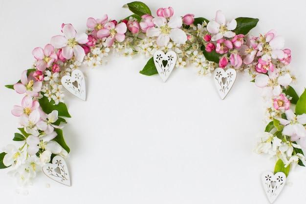 Blüten von vogelkirschen und apfelbäumen sind mit einem bogen und dekorativen weißen herzen gesäumt