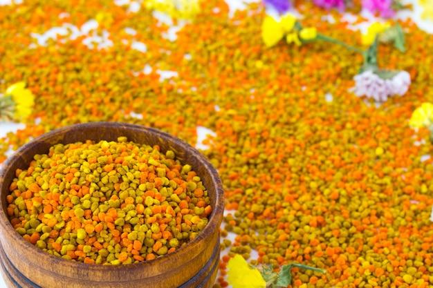 Blütenpollen in einer holzkiste. blumen liegen auf pollen