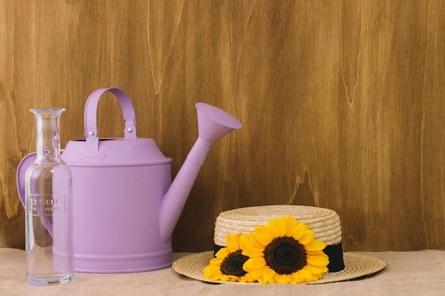 Blütenzusammensetzung mit gießkanne und hut