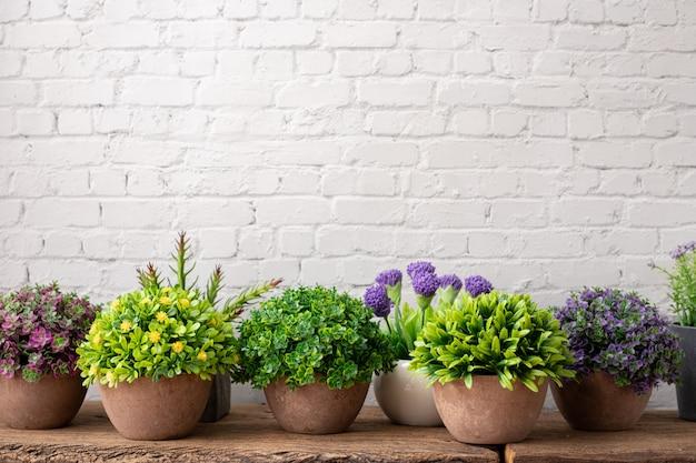 Blume auf holztisch mit backsteinmauer.