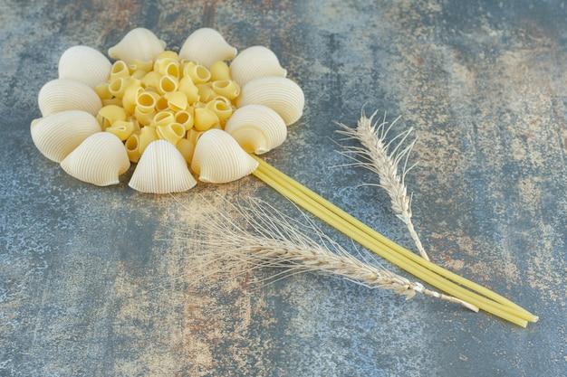 Blume aus nudeln und weizenähre, auf der marmoroberfläche.