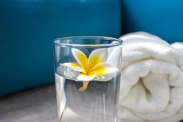 Blume frangipana in einem glas mit wasser nahaufnahme.