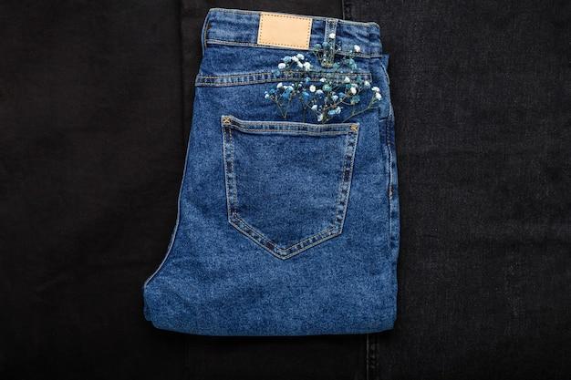 Blume in der jeanstasche. schöne blaue weiße blume in der tasche der blauen jeanshosen auf schwarzem denimhintergrund. frühlings-outfit.
