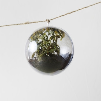 Blume innerhalb der glasverzierung, die von einem seil hängt