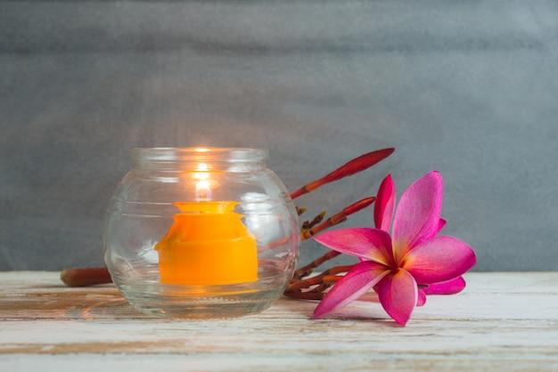 Blume und kerze auf hölzernem badekurorthintergrundkonzept