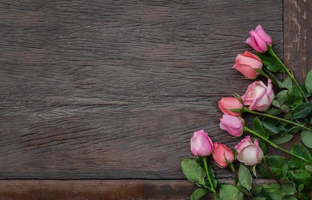 Blumen auf einem hölzernen hintergrund. rosa rosenrahmen auf holzoberfläche mit kopierraum