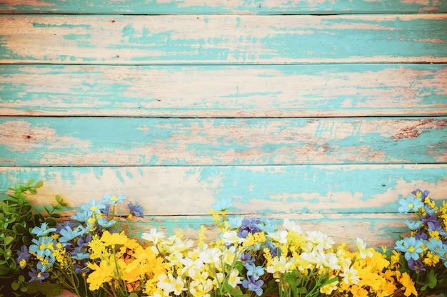 Blumen blühen auf hölzernem hintergrund der weinlese, grenzrahmendesign. weinlesefarbton - konzeptblume des frühlings- oder sommerhintergrundes