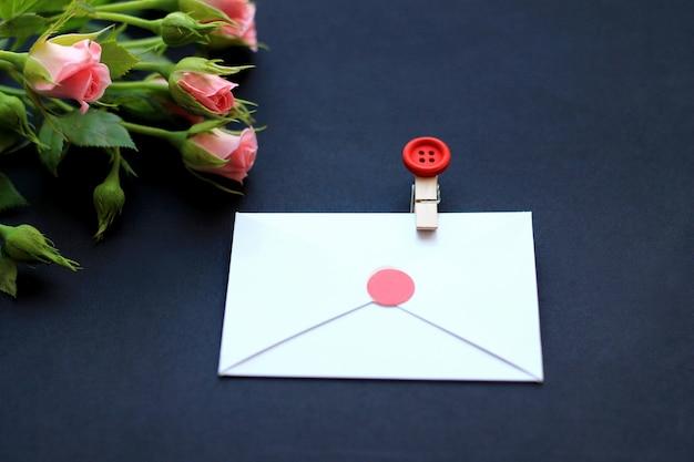 Blumen, dekorative wäscheklammern und papier für anmerkungen über einen dunklen hintergrund. konzept von glückwünschen am feiertag