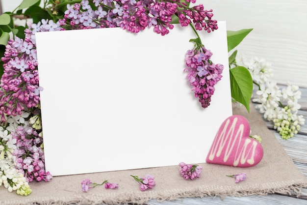 Blumen der purpurroten flieder mit leerem papier auf tabelle
