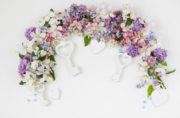 Blumen der vogelkirsche, flieder, vergissmeinnicht und apfelbäume, gesäumt von einem bogen