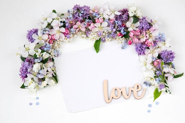 Blumen der vogelkirsche, flieder, vergissmeinnicht und apfelbäume sind mit bogen und papierbögen gesäumt