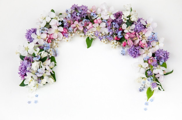 Blumen der vogelkirsche, flieder, vergissmeinnicht und apfelbäume sind mit einem bogen gesäumt