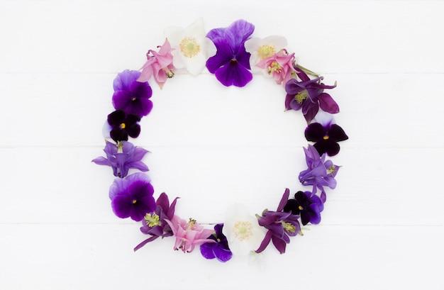 Blumen flaches design. blumiger runder rahmen, blumenkranz mit violetten, lila, rosa weißen blüten. vorlage mit kopierraum auf weißem holzbrett