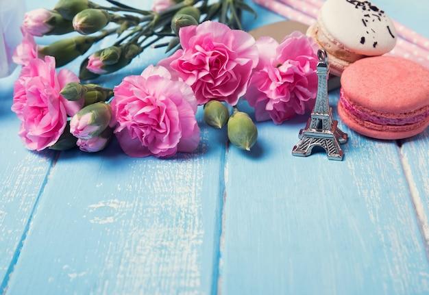 Blumen, französischer macaron und andenken eiffelturm auf dem blauen farbigen hintergrund