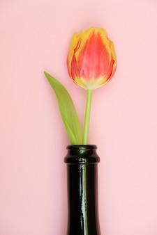 Blumen in der flasche auf einem zarten rosa hintergrund. das konzept des jubiläums