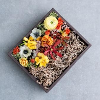 Blumen in der geschenkbox auf grauem hintergrund. blumenstrauß von verschiedenen blumen in der alten hölzernen rustikalen kiste, draufsicht.