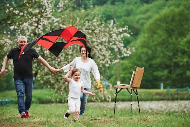 Blumen in der hand. positives weibliches kind mit großmutter und großvater, die mit rotem und schwarzem drachen in den händen draußen laufen