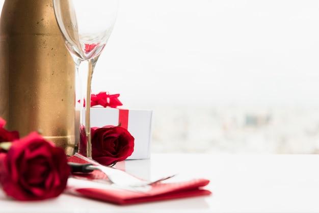 Blumen in der nähe von glas, geschenk und eine flasche zu trinken