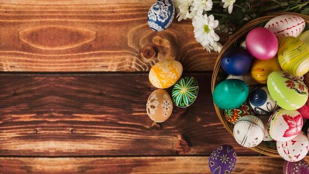 Blumen in der nähe von korb mit eiern